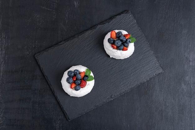 Gâteau à la meringue aux baies fraîches. dessert de baies sur fond noir, vue de dessus.