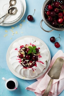 Gâteau meringué maison pavlova avec crème fouettée, cerise fraîche et sauce sur une surface de texture en béton léger. vue de dessus,