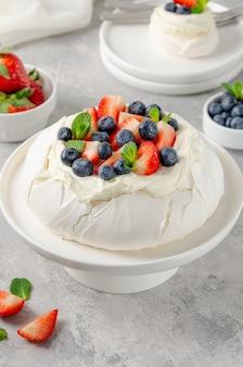 Gâteau de meringue pavlova avec crème fouettée et baies fraîches sur le dessus sur une plaque blanche