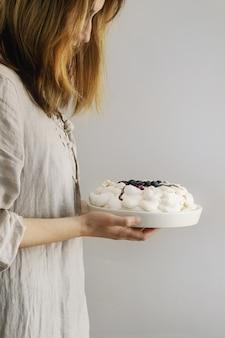 Gâteau de meringue pavlova en mains féminines