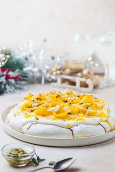 Gâteau meringué pavlova à la mangue fraîche et aux fruits de la passion et crème fouettée sur fond d'ardoise, de pierre ou de béton