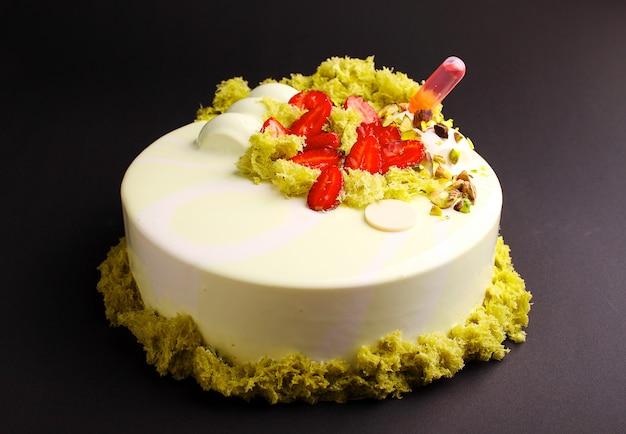 Gâteau à la mousse de baies avec glaçure miroir. décoré de fraises et de biscuits moléculaires. sur le fond noir