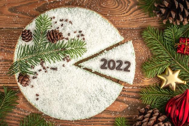 Gâteau mousse blanc festif recouvert de flocons de noix de coco, imitant la neige. sur le morceau de gâteau, le numéro 2022 est éteint avec du chocolat. concept d'une nouvelle année.