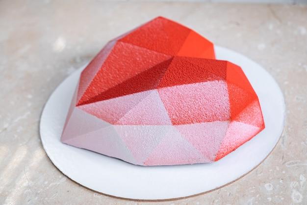 Gâteau mousse coeur rouge à facettes avec revêtement en velours sur une table en marbre rose tendre.