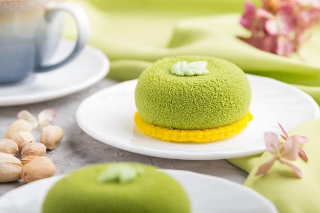 Gâteau mousse verte à la crème de pistache et une tasse de café sur une surface en béton gris. vue latérale, mise au point sélective.