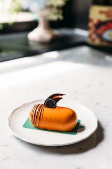Gâteau mousses au thé thaïlandais classique décoré avec du chocolat dans une assiette blanche sur une table en marbre.