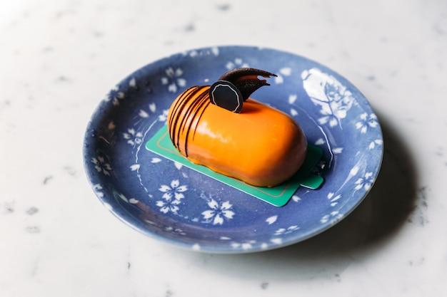 Gâteau mousses au thé thaïlandais classique décoré avec du chocolat dans une assiette bleue sur une table en marbre.