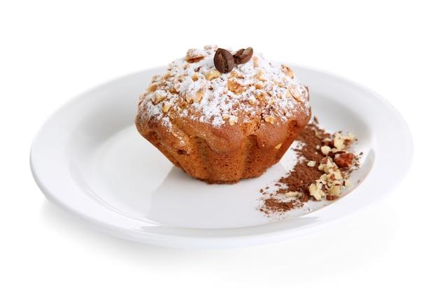 Gâteau muffin savoureux avec du sucre en poudre et du cacao sur plaque, isolé sur blanc