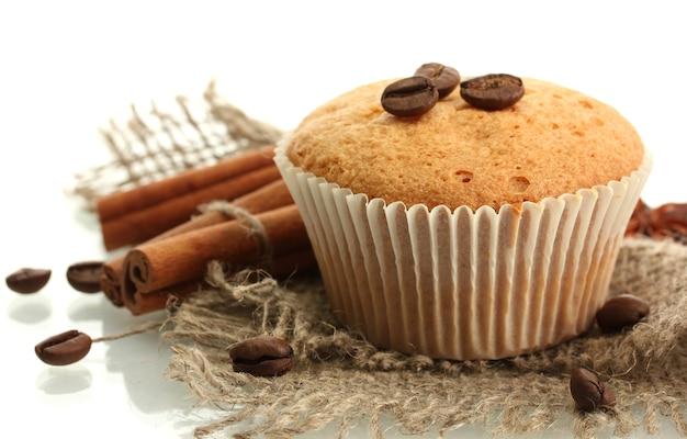 Gâteau muffin savoureux sur toile de jute, épices et graines de café, isolé sur blanc