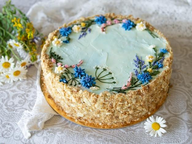 Gâteau napoléon à la crème vanille, décoré de fleurs de crème au beurre