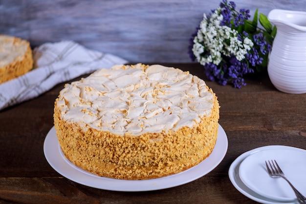 Gâteau napoléon avec fleurs et assiettes blanches