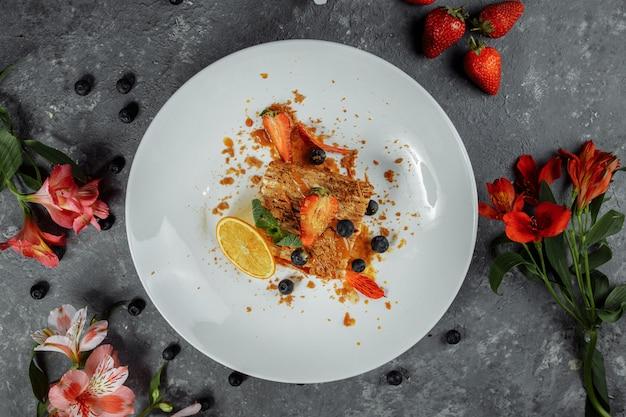 Gâteau napoléon à la sauce au caramel. délicat gâteau feuilleté à la crème anglaise et à la sauce au caramel décoré de fraises, de bleuets et de menthe
