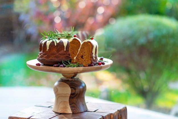 Gâteau de noël au caramel, en coupe, décoré de chocolat blanc, canneberges et romarin sur un support en bois. pâtisseries festives. mise au point sélective douce. horizontal