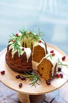 Gâteau de noël au caramel, en coupe, décoré de chocolat blanc, canneberges et romarin sur un support en bois. pâtisseries festives. mise au point sélective douce. verticale