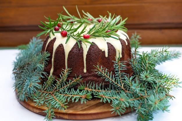 Gâteau de noël au caramel, décoré de chocolat blanc, canneberges et romarin pâtisseries festives. mise au point sélective douce.