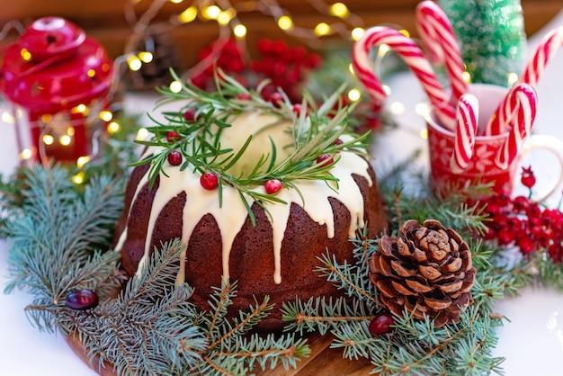 Gâteau de noël au caramel, décoré de décorations au chocolat blanc, aux canneberges, au romarin et au nouvel an. pâtisseries festives. mise au point sélective douce. horizontal