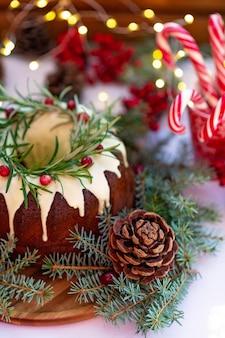Gâteau de noël au caramel, décoré de décorations au chocolat blanc, aux canneberges, au romarin et au nouvel an. pâtisseries festives. mise au point sélective douce. verticale