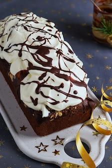 Gâteau de noël au chocolat, décoré de glaçage à la crème fouettée et de fondant