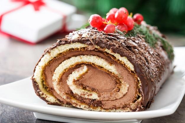 Gâteau de noël au chocolat avec groseille sur bois.