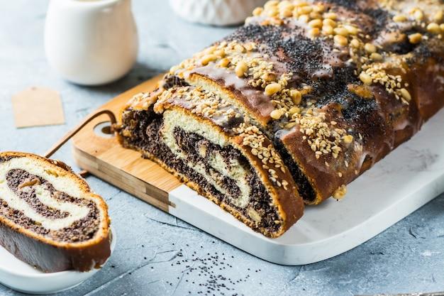 Gâteau de noël aux graines de pavot, gâteau aux graines de pavot tranché recouvert de glaçage et décoré de raisins secs et de noix. gâteau de noël traditionnel de pologne. plat de noël. la veille de noël. noël
