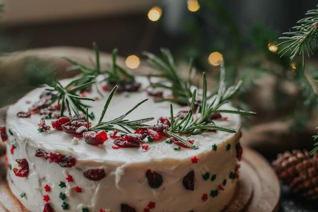 Gâteau de noël à la crème au fromage blanc, décoré de canneberges et de romarin.