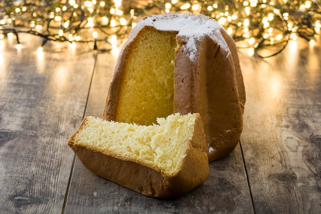 Gâteau de noël pandoro avec du sucre et de la lumière de noël sur une table en bois