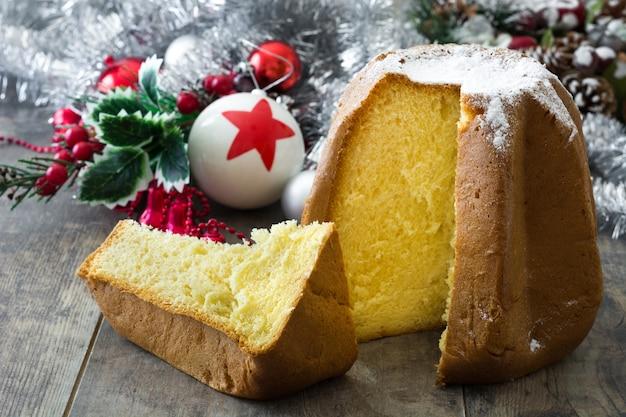 Gâteau de noël pandoro avec du sucre et des ornements de noël sur une table en bois
