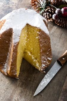 Gâteau de noël pandoro avec du sucre sur une table en bois