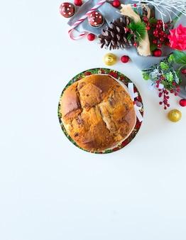 Gâteau de noël panettone au chocolat italien avec des cônes en épingle à cônes de décorations babiole sur un fond en bois.
