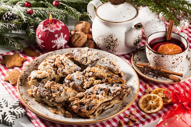 Gâteau de noël en tranches, thé de noël et décorations de noël sur table de vacances