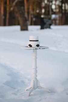 Gâteau en noir et blanc, debout sur un support dans une forêt d'hiver sur la neige
