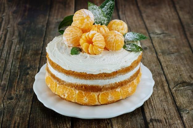 Gâteau nu aux mandarines avec des feuilles sur fond rustique.