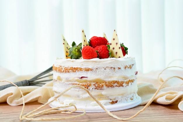 Un gâteau nu avec des fraises et des morceaux de chocolat sur le dessus, dessert sucré