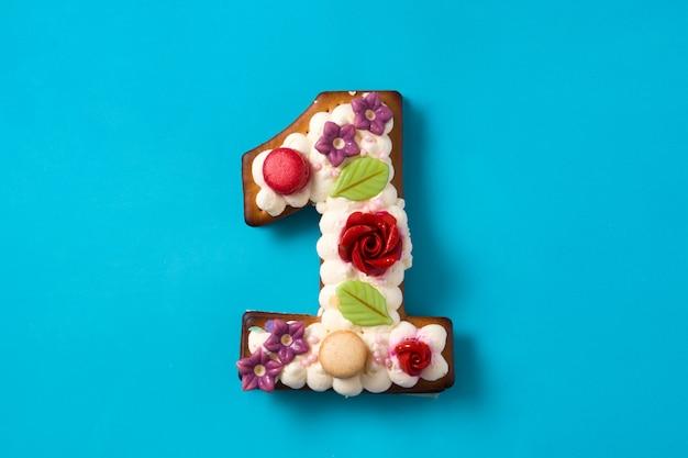 Gâteau numéro un décoré de fleurs et de biscuits