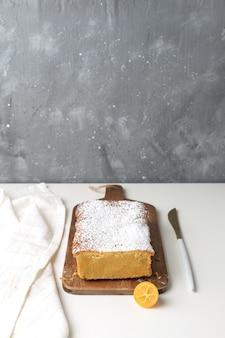 Gâteau orange aux kumquats sur une planche à découper en bois