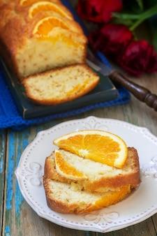 Gâteau à l'orange, décoré de tranches d'orange sur fond d'oranges juteuses et d'un bouquet de tulipes. style rustique.