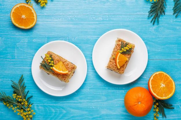 Gâteau à l'orange décoré de tranches d'orange fraîches et de fleurs de mimosa à la lumière