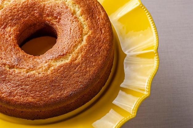 Gâteau orange fait maison dans un beau support de gâteau jaune.