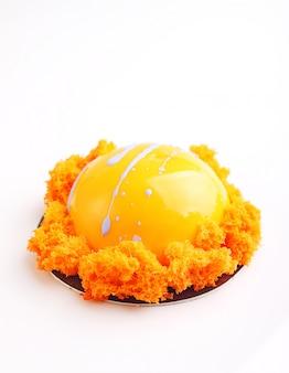 Le gâteau orange à la glaçure miroir est décoré avec un biscuit moléculaire. fond blanc