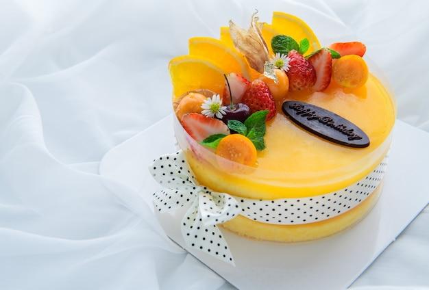 Gâteau orange avec joyeux jour de naissance et garni d'orange, de fraise, de myrtille et de groseille du cap sur fond de tissu blanc, espace de copie et concept de dessert