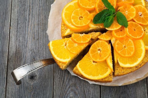 Gâteau orange et mandarine avec polenta, à l'envers sur le vieux bois