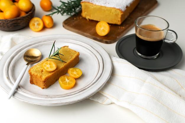 Gâteau orange servi, planche à découper en bois, café expresso frais kumquats