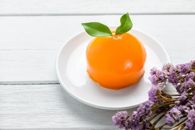Gâteau orange sur une table en bois blanche