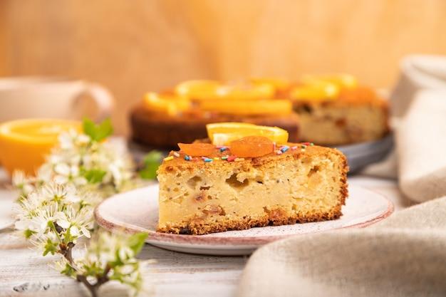 Gâteau à l'orange et une tasse de café sur un bois blanc