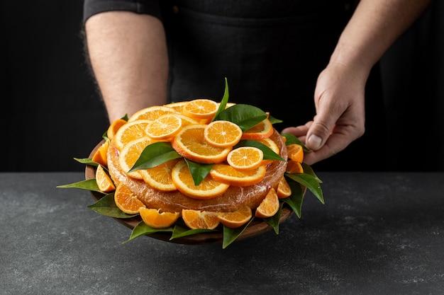 Gâteau à l'orange tenu par le chef pâtissier