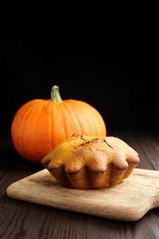 Gâteau de pain à la citrouille maison sur planche à découper en bois avec de la citrouille fraîche sur fond noir. repas de thanksgiving.