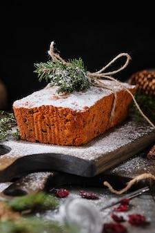 Gâteau de pain d'épice du nouvel an au kumquat, baies séchées et fruits. un dessert festif décoré de brindilles d'épinette, de baies et de fruits frais.