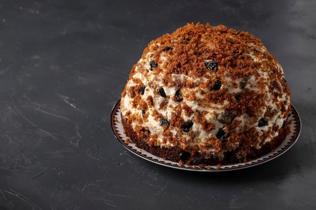 Gâteau pancho avec crème sure, noix, pruneaux et chocolat sur une surface sombre, gros plan, espace de copie