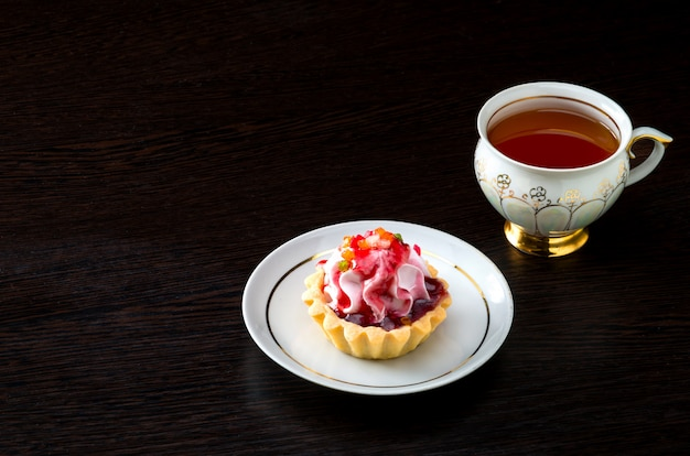 Gâteau de panier avec de la confiture dans l'assiette et du thé