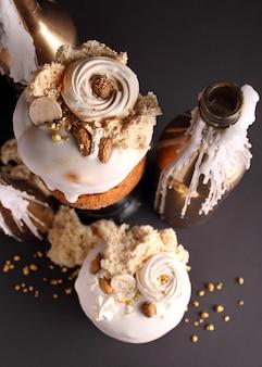 Le gâteau de pâques aux raisins secs et aux fruits confits en émail blanc est décoré de noix, de biscuit moléculaire et de meringue